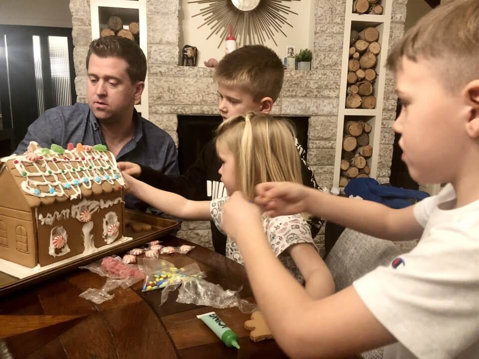 Family time with three children building a gingerbread house