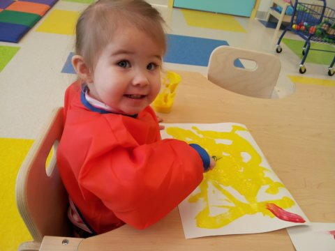 Child painting with yellow paint
