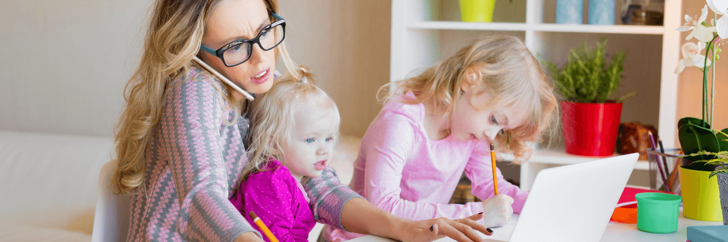 Mother working at home with two kids