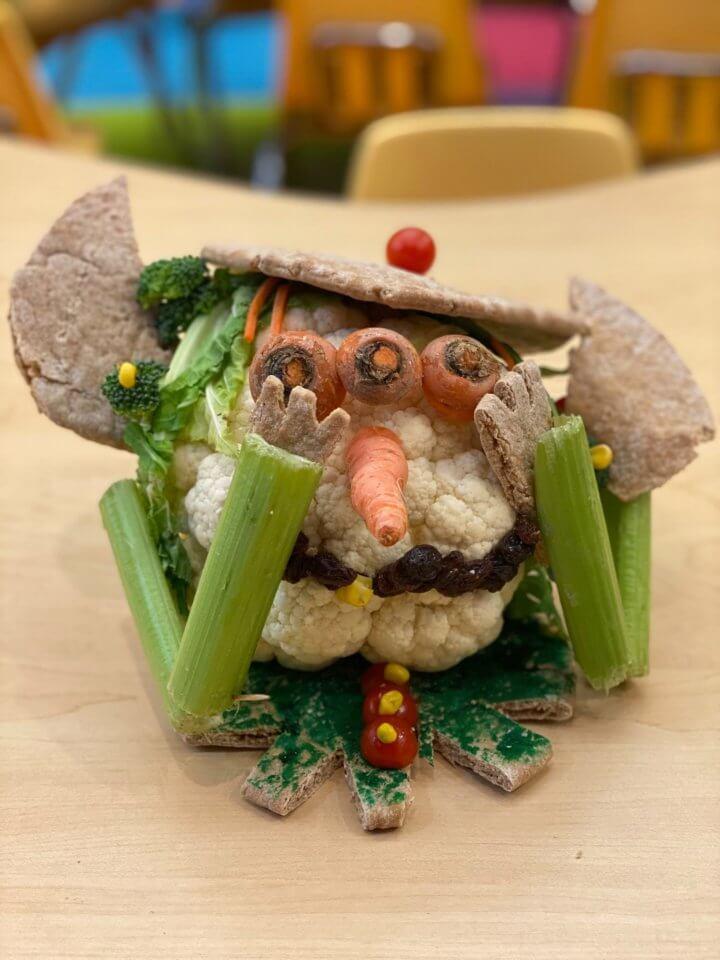 Creepy creature made out of celery, cauliflower, pita
