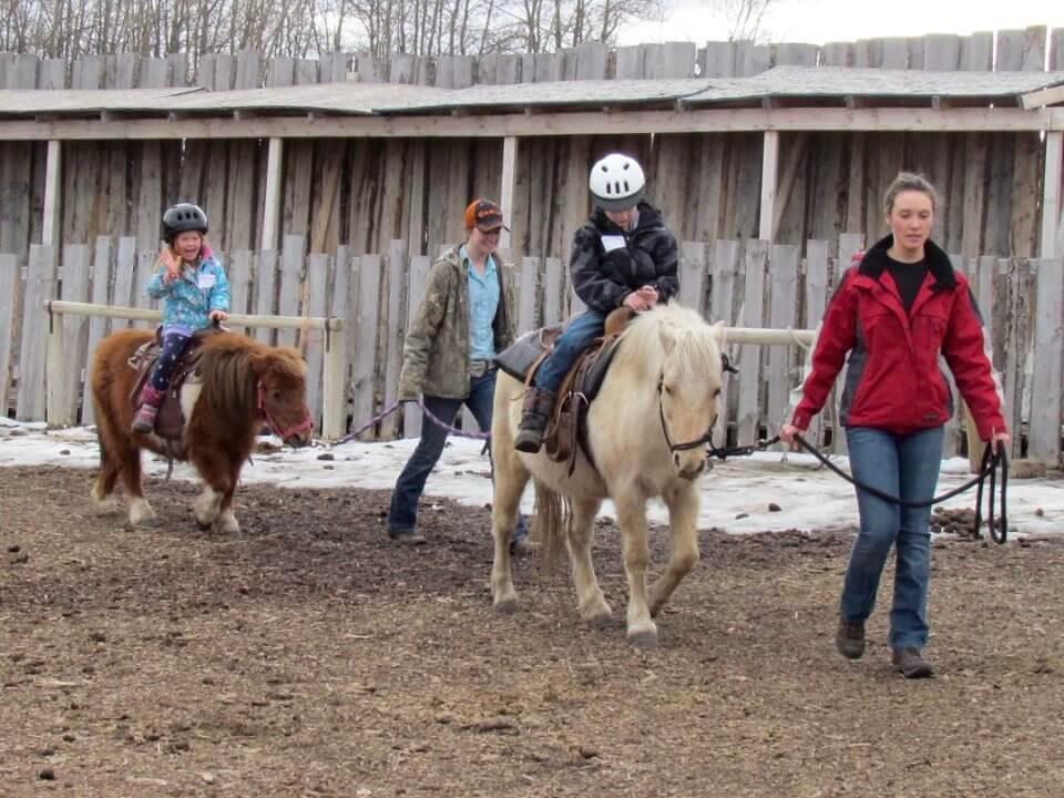 child riding horses