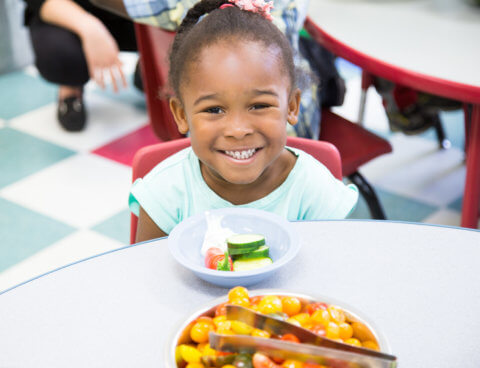 Child smiling eating healthy snack