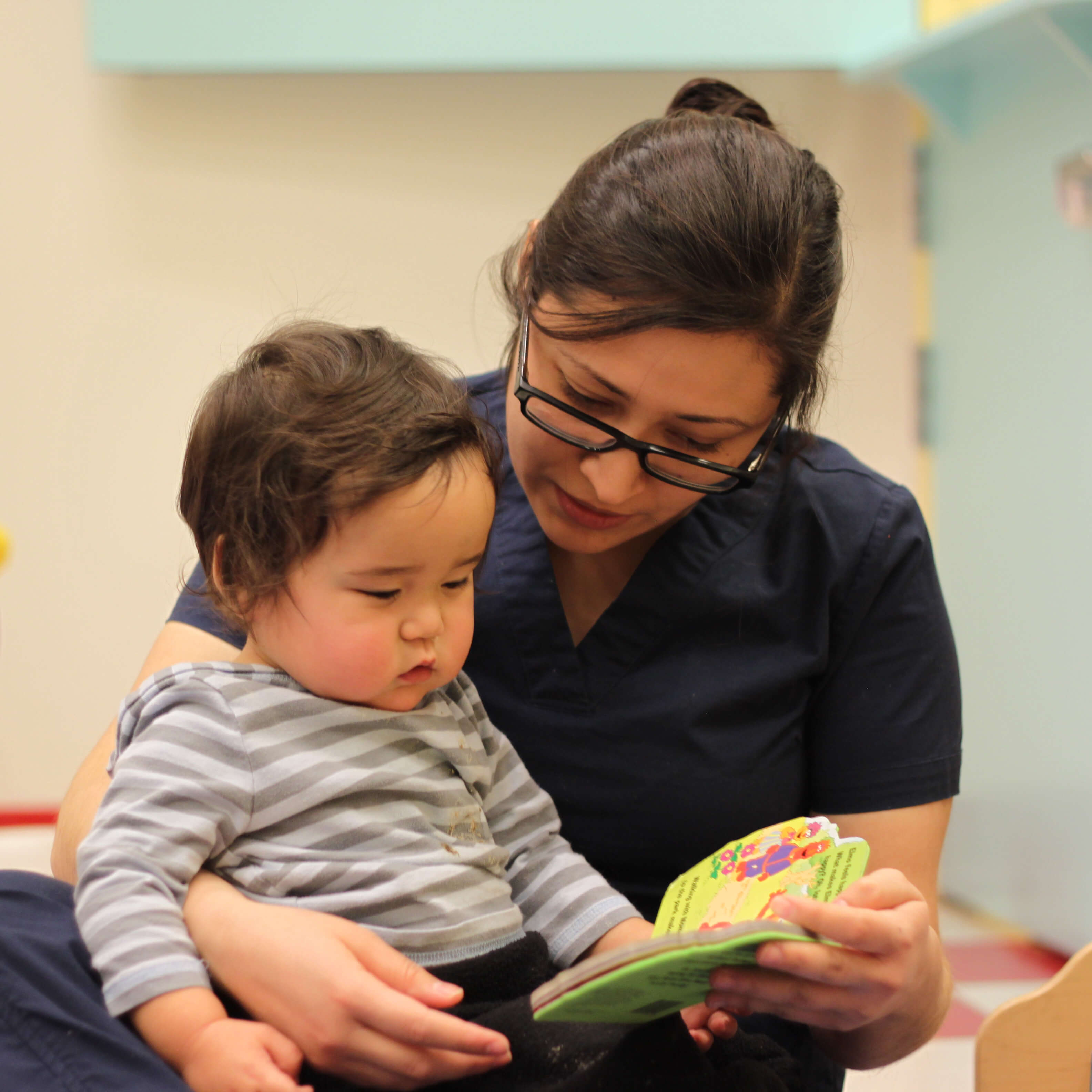 childcare educator with child reading preschool book