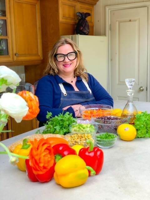 Chef lisa standing outside with vegetables and fruit