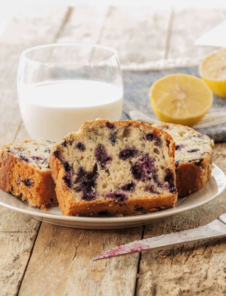 Lemon and blueberry loaf on a wooden table with a glass of milk