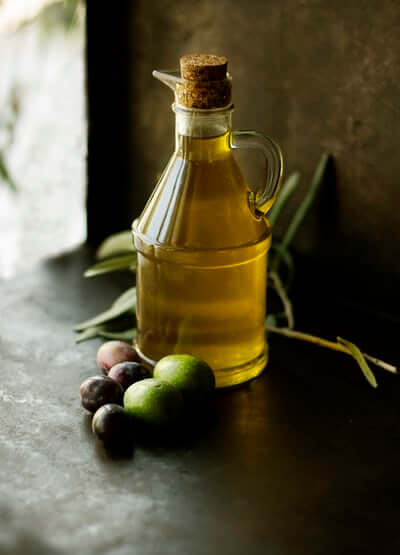 Bottle of olive oil with olives beside