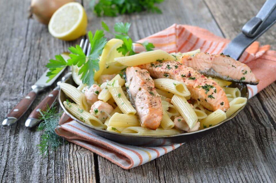 Salmon pasta on a wood table with lemon