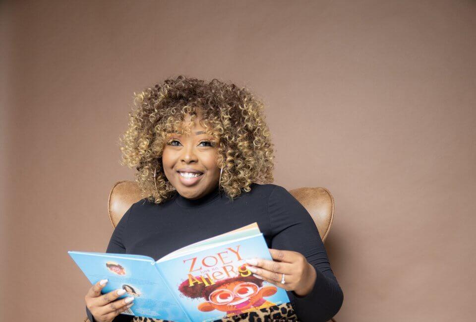 Anisha angella, black shirt, brown background holding children's book.