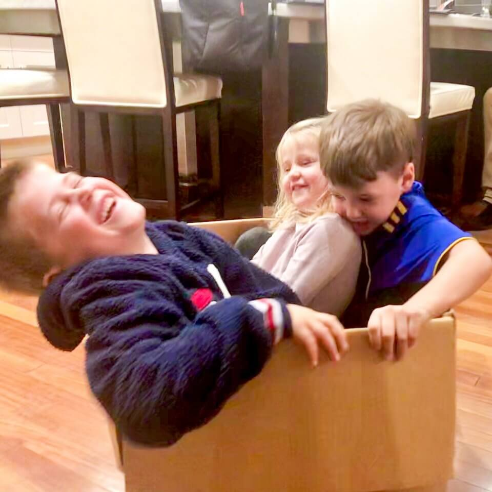 Three children playing together in a box