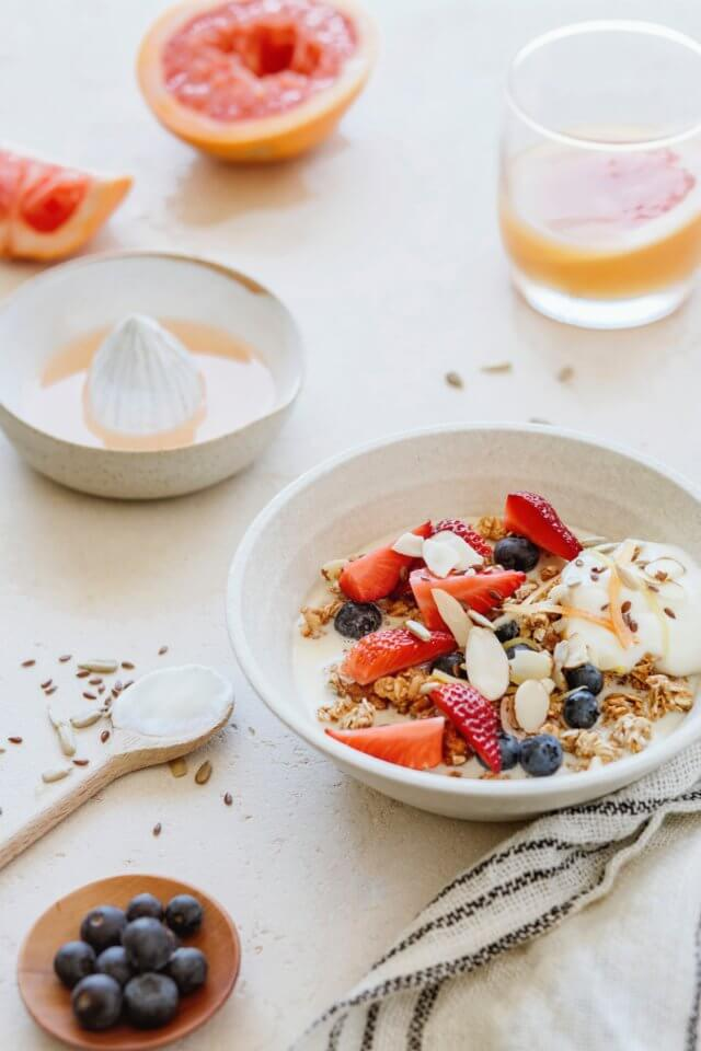 White table with breakfast - yogurt, granola, grapefruit