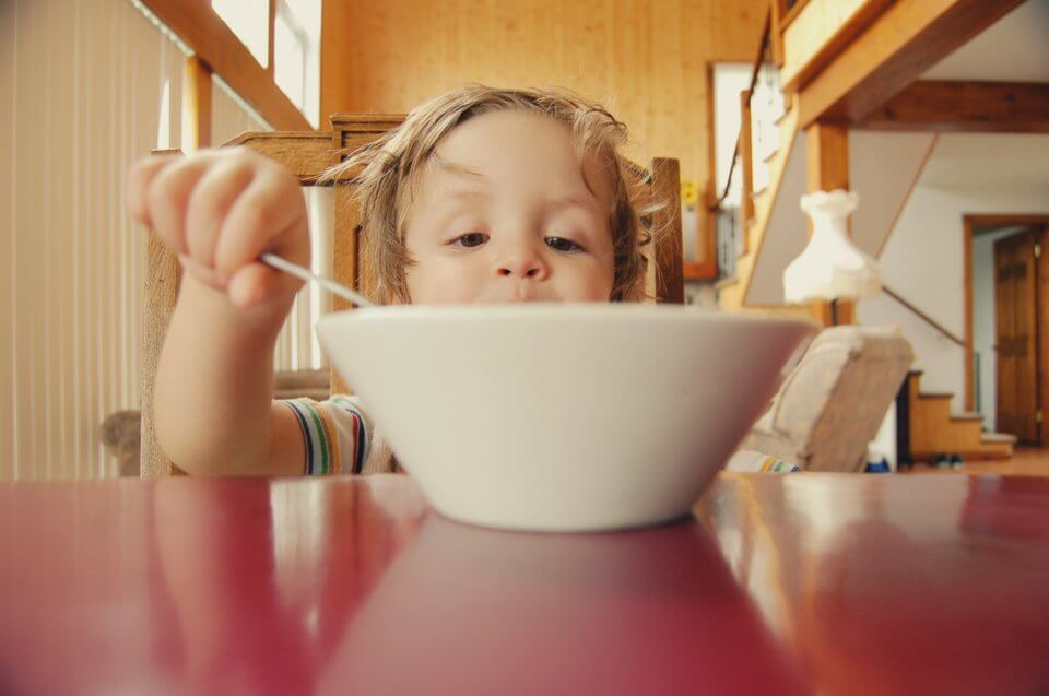 Child sitting at a table eating breakfast