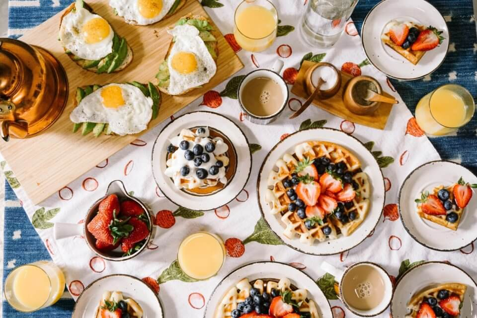 Brunch on table with waffles and eggs