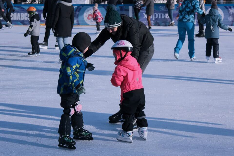 Two children on skates with an adult