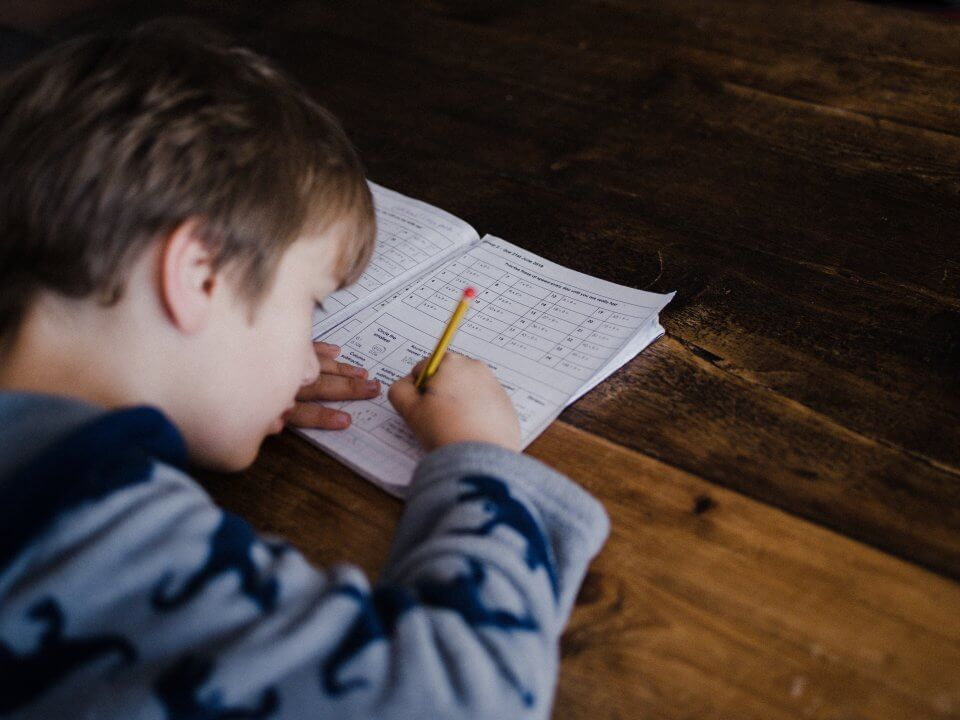 Child doing school work from home on a wooden table.