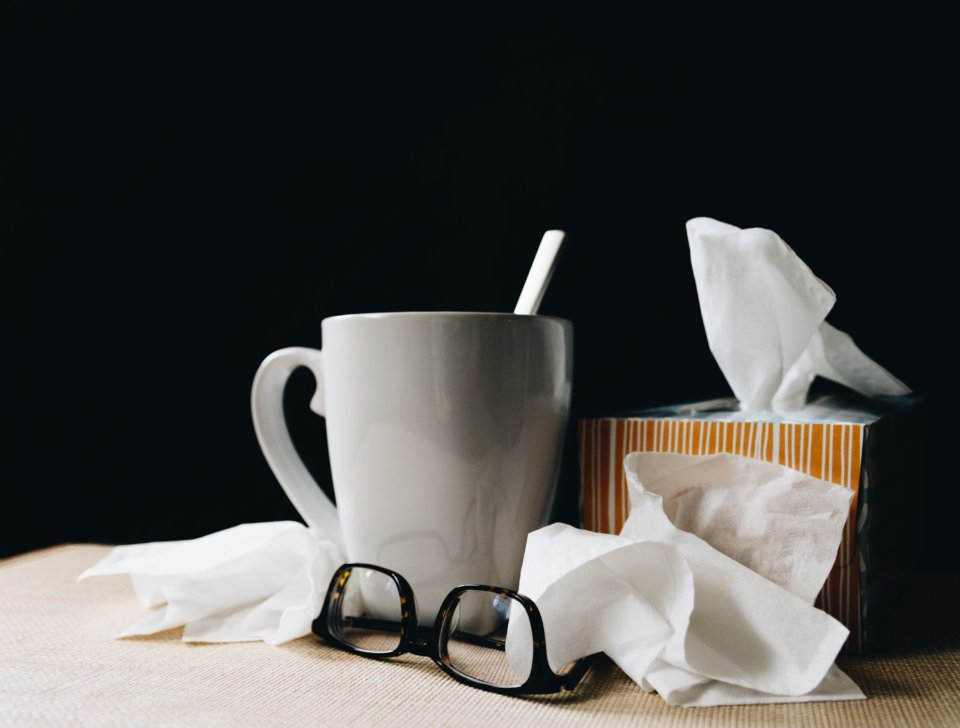 Mug of tea with tissues and glasses