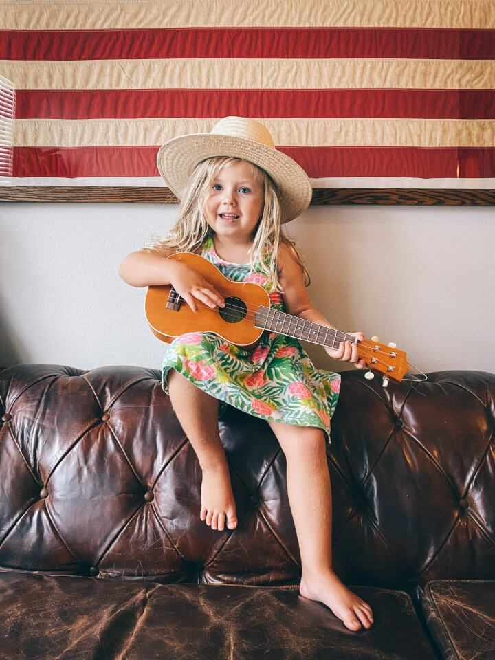 Child playing the guitar on a couch
