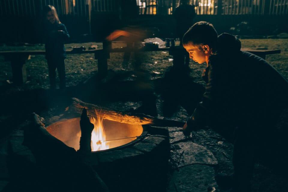Boy outside by a fire in a winter coat
