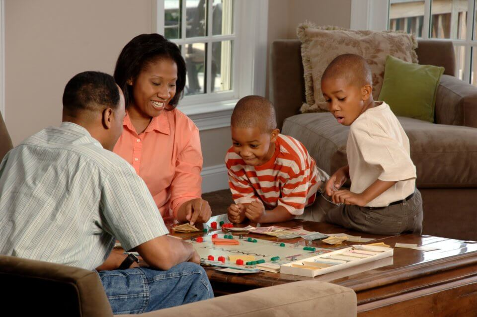 Family of four playing a board game together