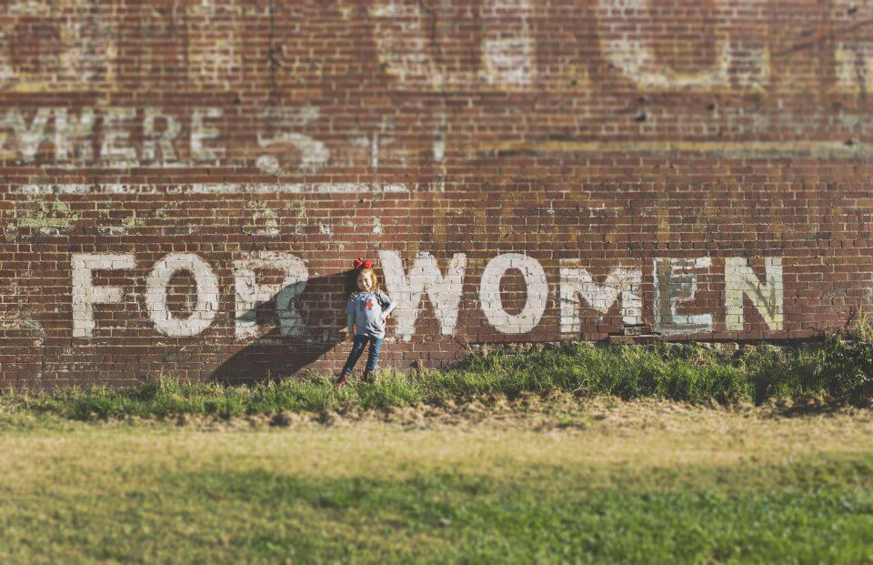 Little girl standing in front of a for women wall