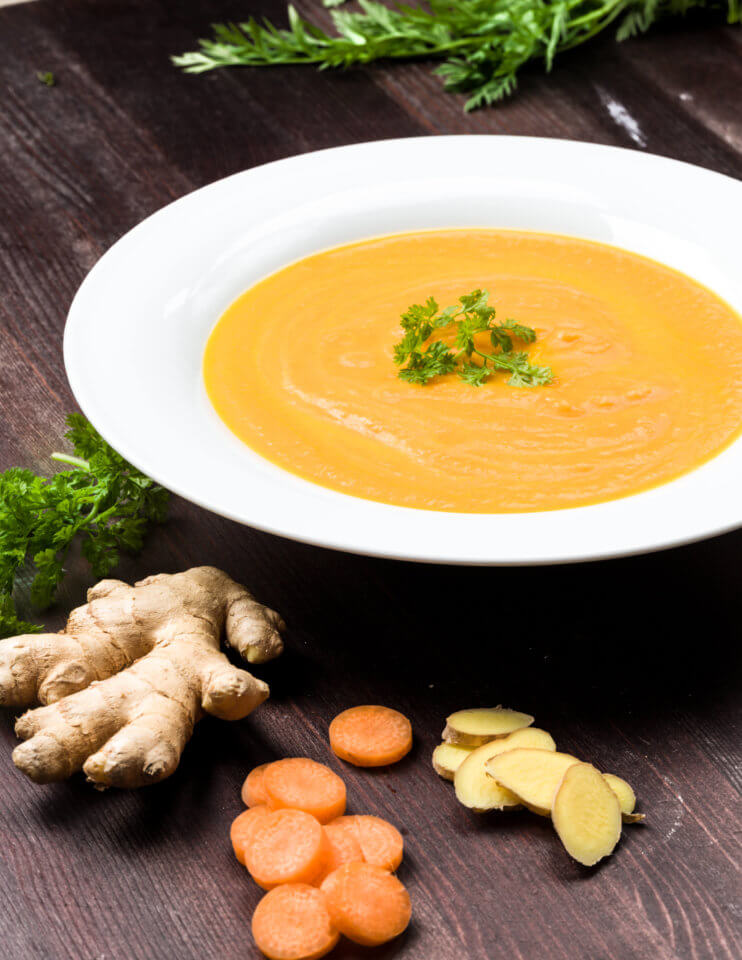 Ginger carrot soup in a white bowl on a wooden table