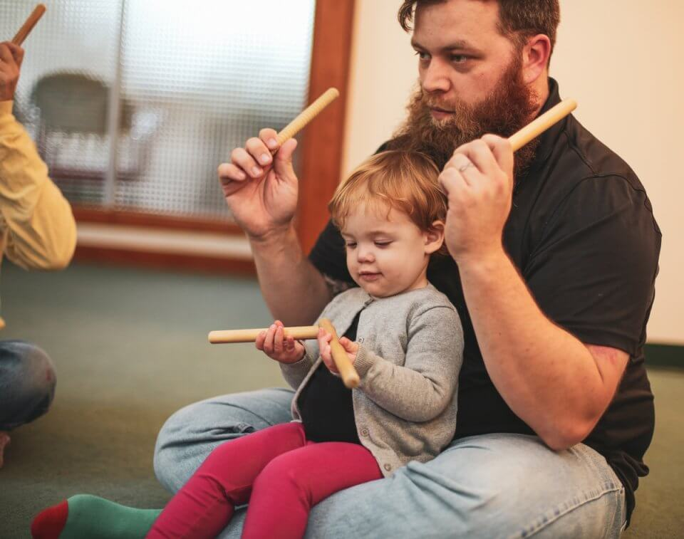 Child and father playing music together.