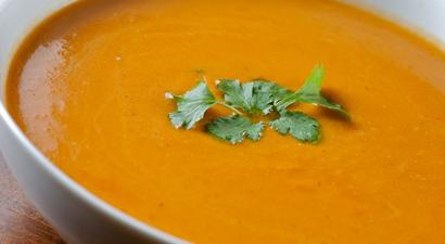 Butternut Squash soup in a white bowl with cilantro on top