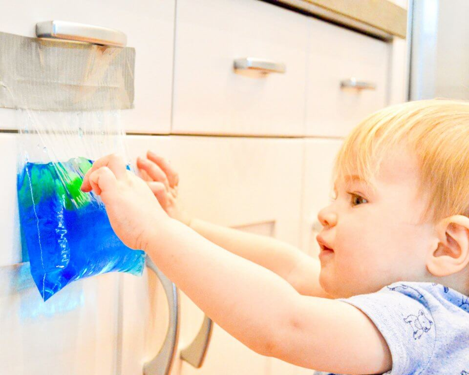 A child is playing with a sensory bag taped filled with hair gel, glitter and food colouring into a secure zipped plastic bag, taped on a kitchen cabinet.