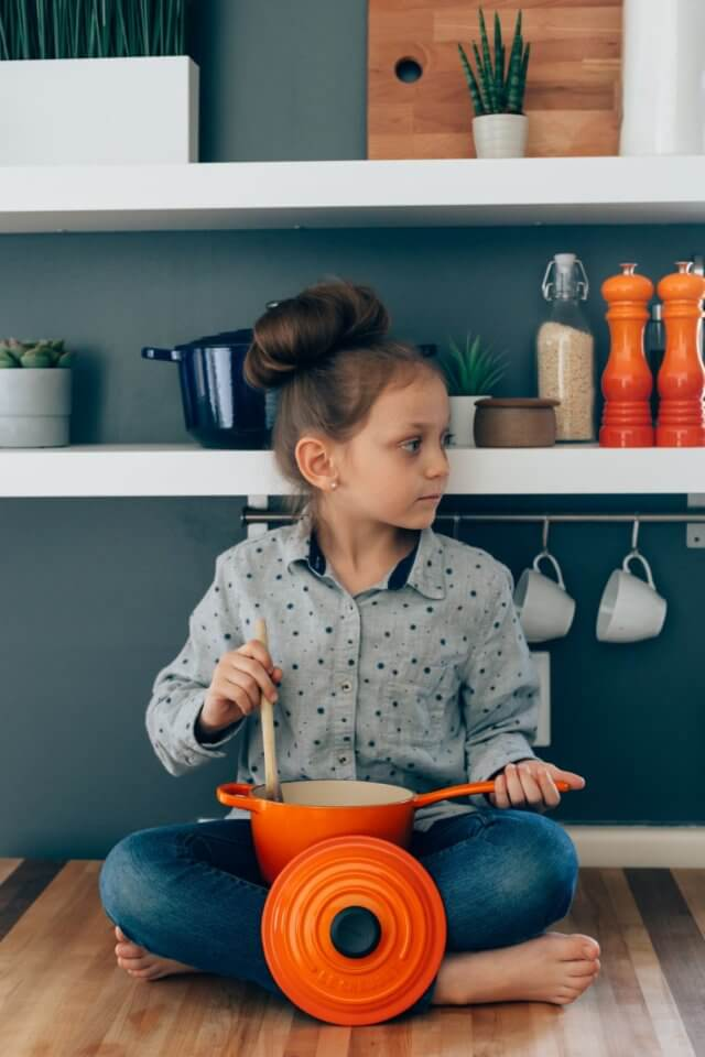 Child sitting on the floor eating food out of an orange pot