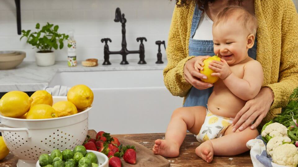 Baby sitting on the kitchen counter holding a lemon