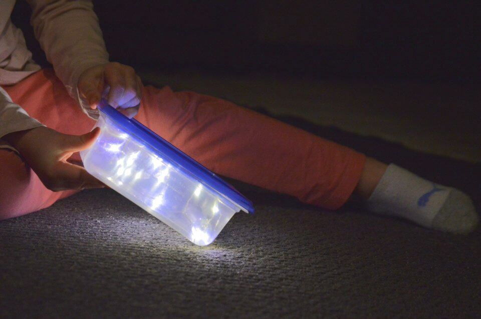 Child playing with lights in a tupperware container.
