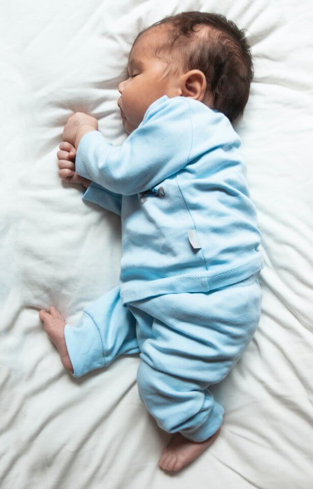 Newborn baby in blue outfit on a white bed