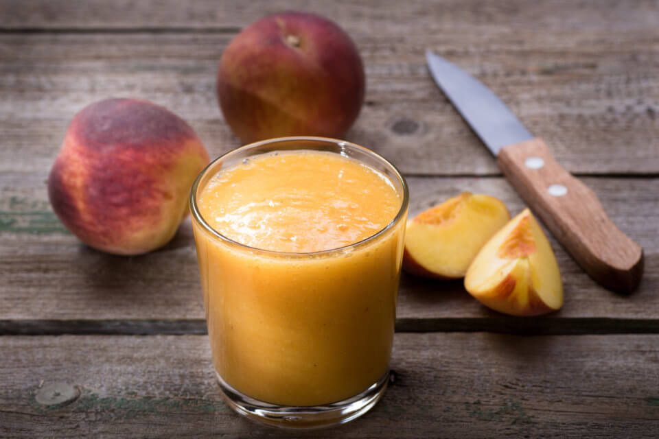 Peach smoothie on a wooden table