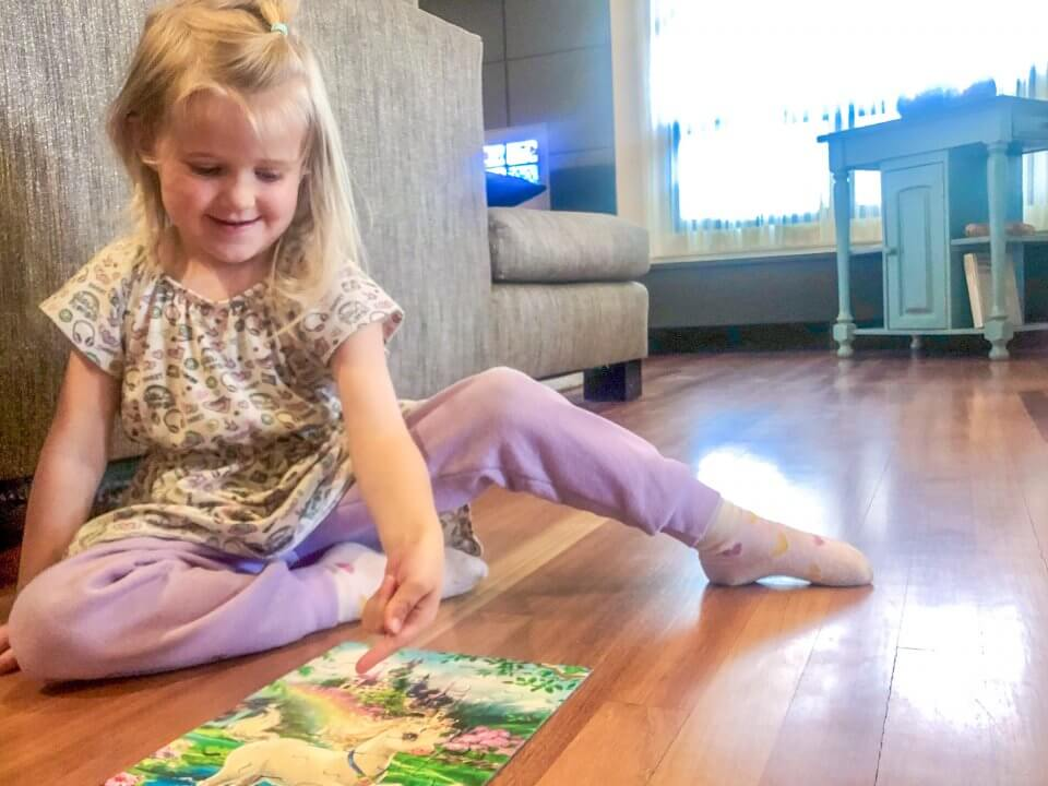 Child doing a puzzle with a unicorn on it