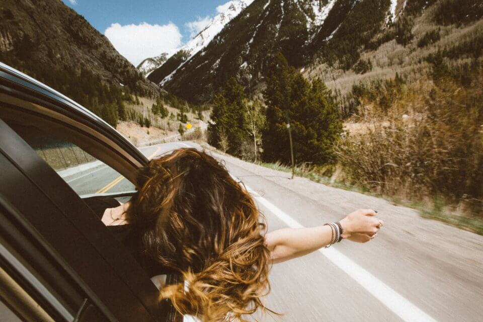 Road trip - woman with her head out of the car in the mountains