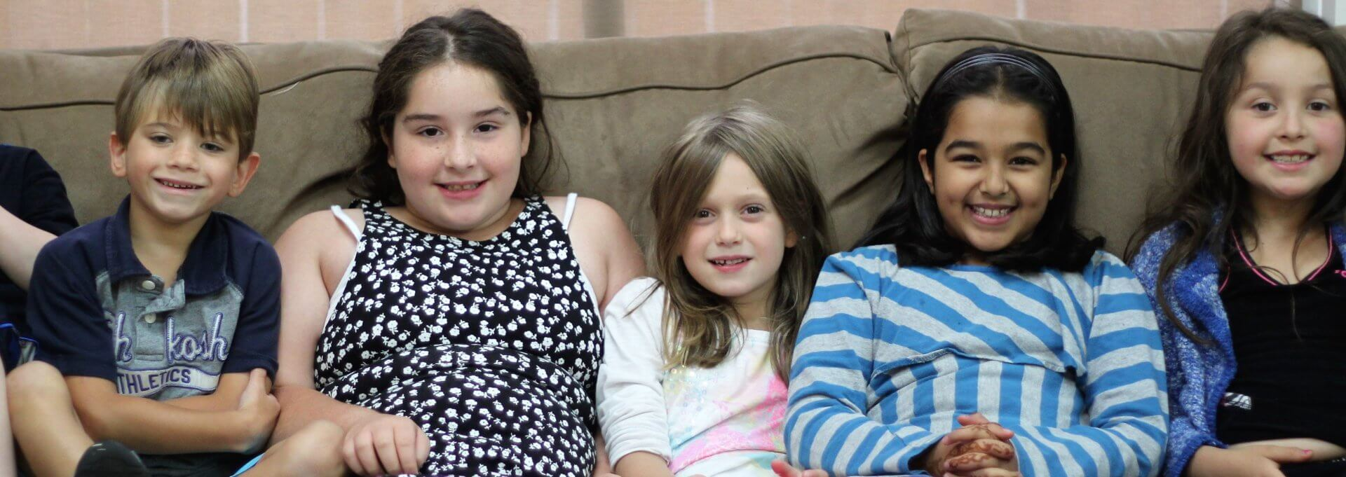 Children smiling on couch