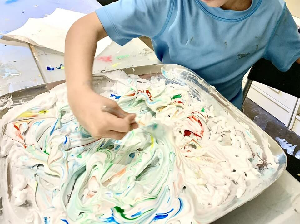 Child doing a shaving cream painting at home.