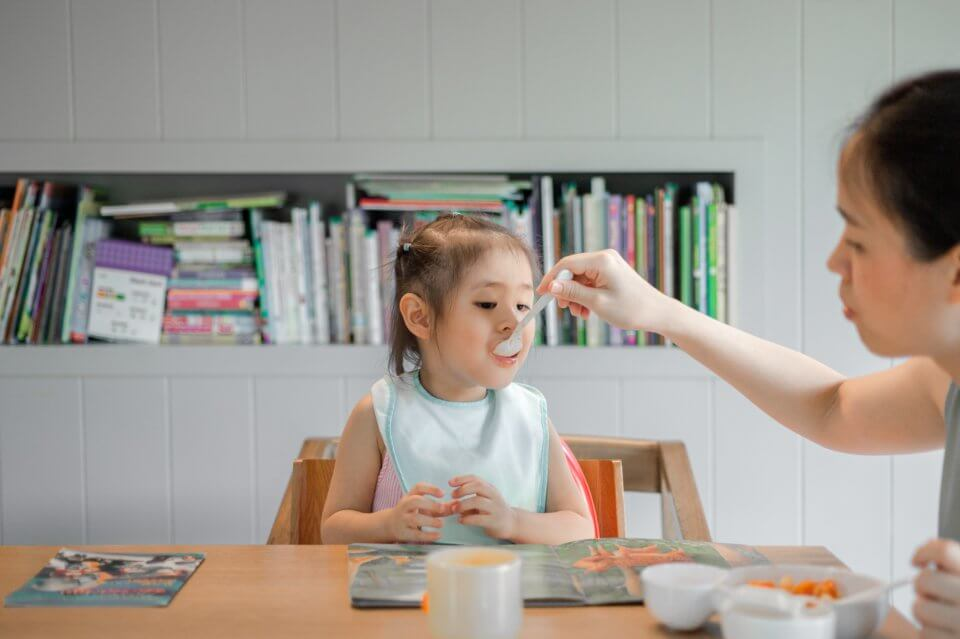 Child being fed by a spoon by her mother