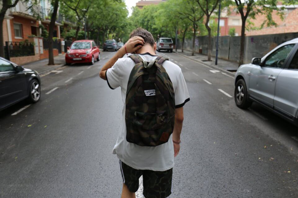 Teenager walkning down the street wearing a backpack