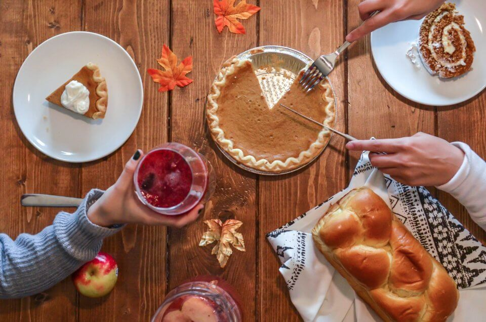 Thanksgiving celebration with pumpkin pie, apples, and bread.