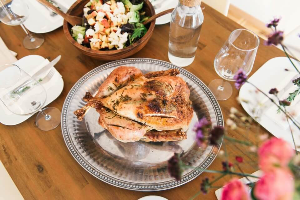 Turkey on a silver platter surrounded by flowers and salad.