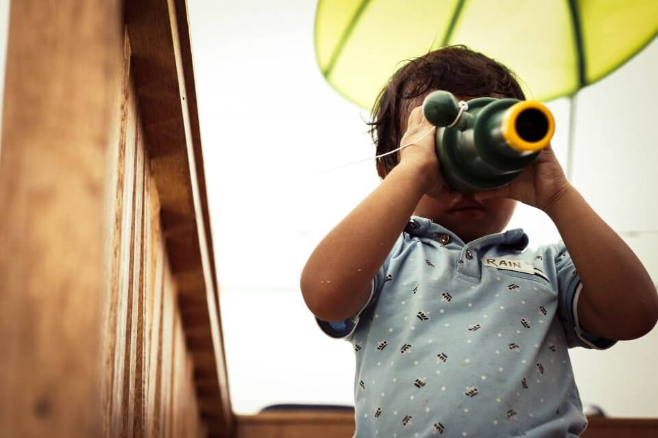 toddler looking through a telescope