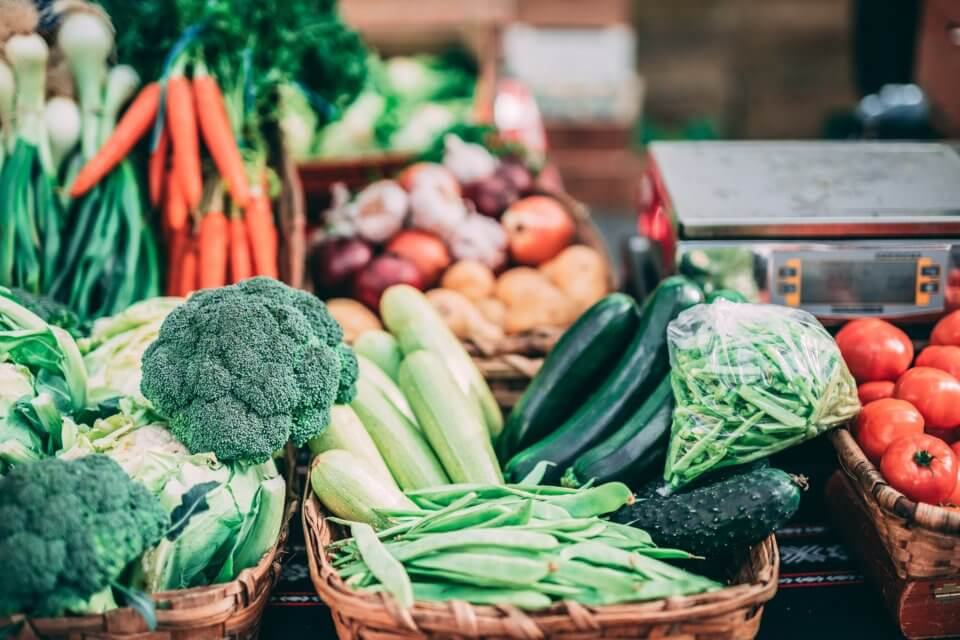 Variety of green vegetables, carrots, onions and tomatoes at the grocery store