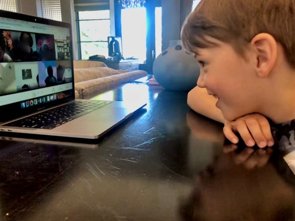 Child doing a video call with family members while at home