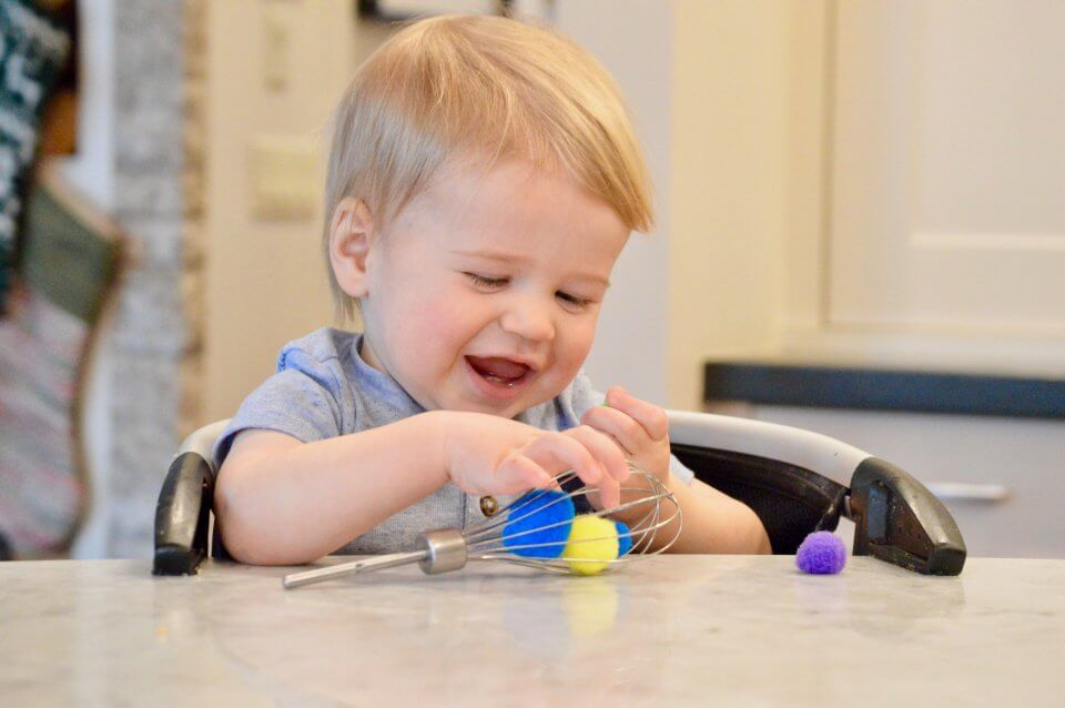 A child is playing with pom poms in a whisk, exploring his senses.